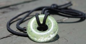 Picture of a UVO Green Necklace on a black cord in on a dock